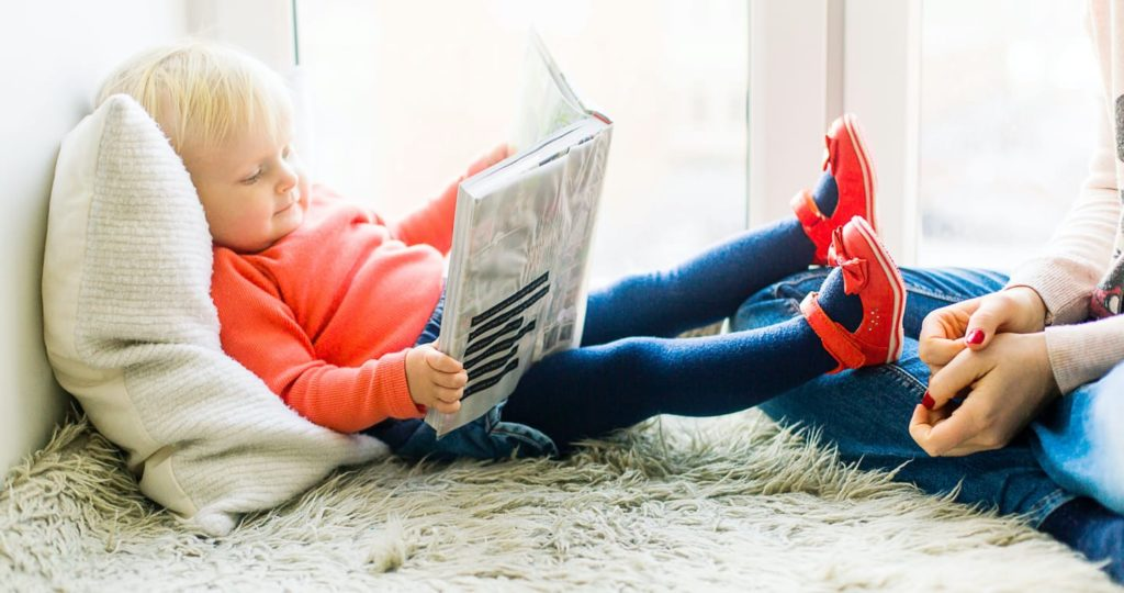 Toddler girl reading a book with her mom while laying down